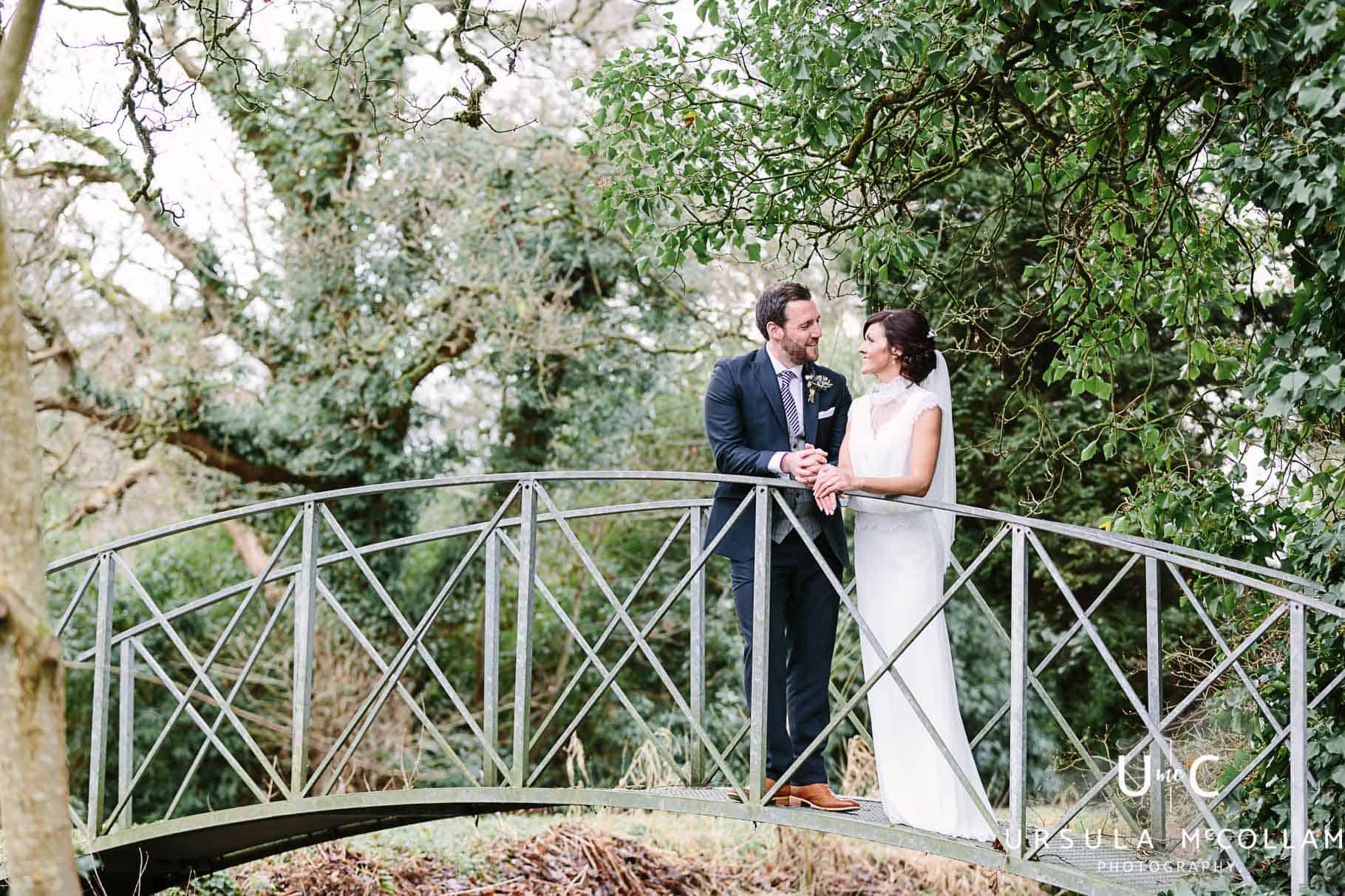 Bride and groom looking lovoingly at each other on a bridge in Tullyglass Country house by Northern Ireland Wedding Photographer