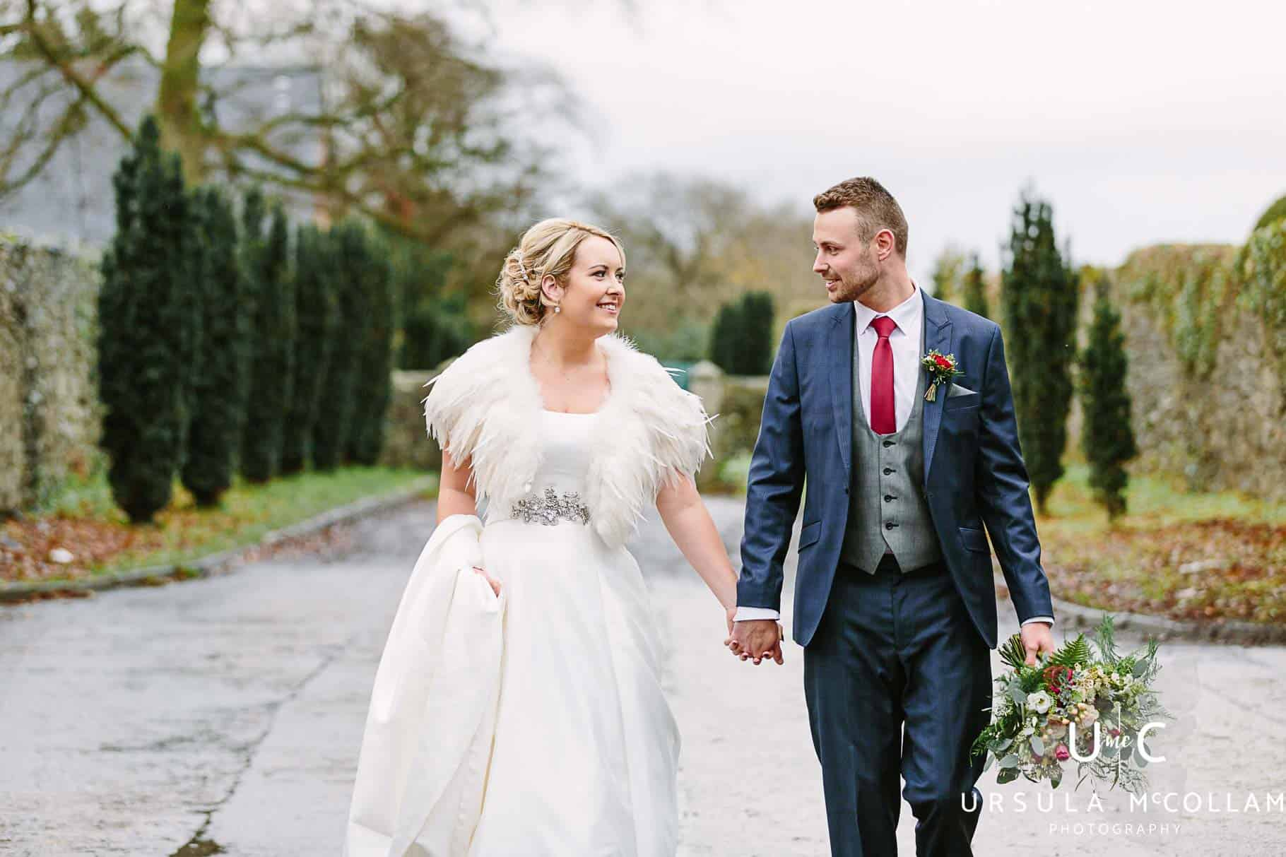 Bride and groom walking hand in hand at Clandeboye lodge