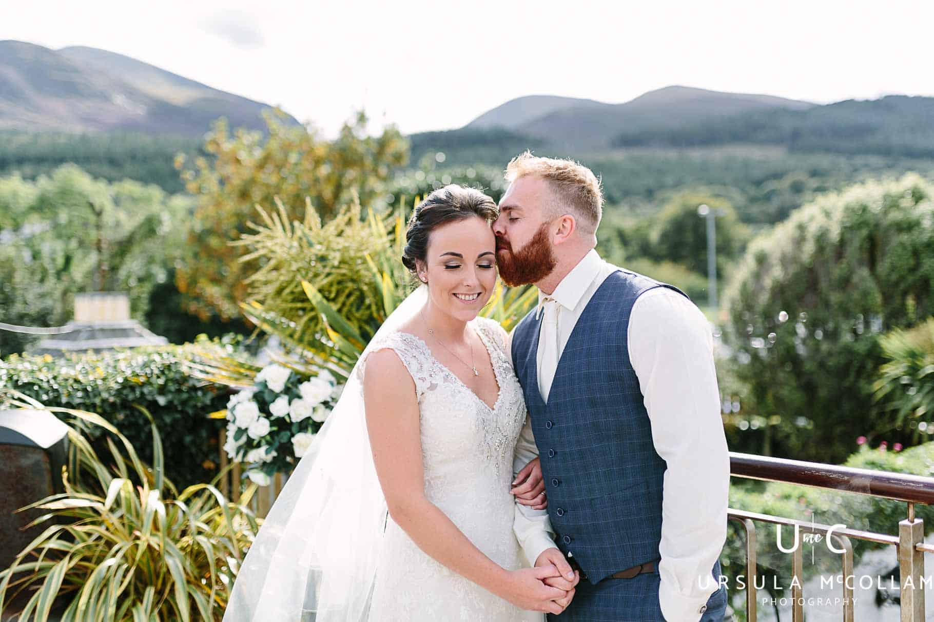 Groom kissing his bride at Hugh McCann's, Newcastle with the Mourne Mountains in the background.