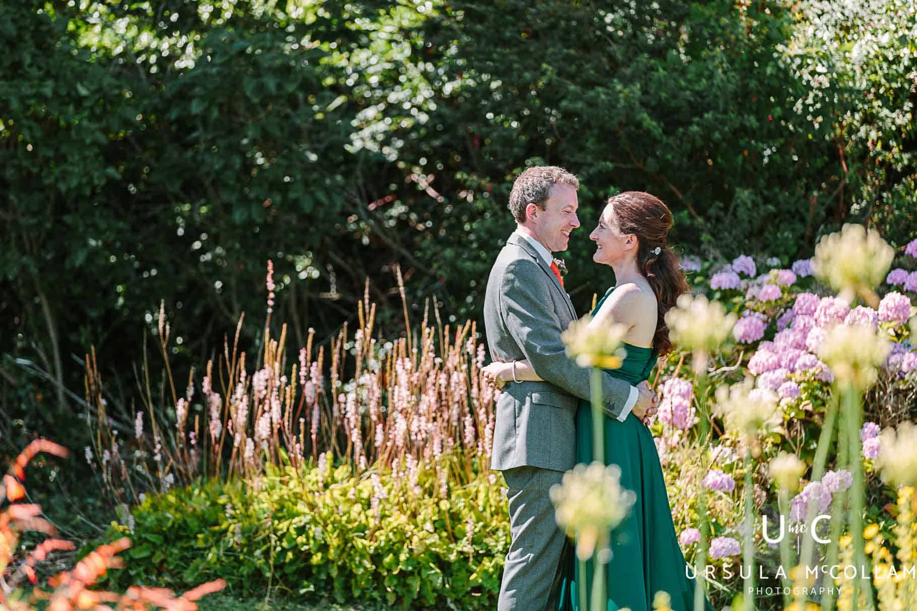 Bride in a green dress cuddling her groom