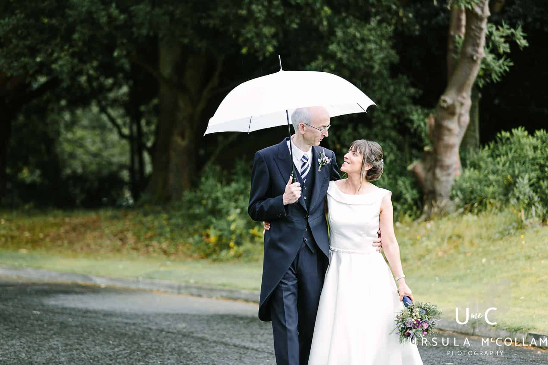 Bride and Groom walking along under a white umbrella