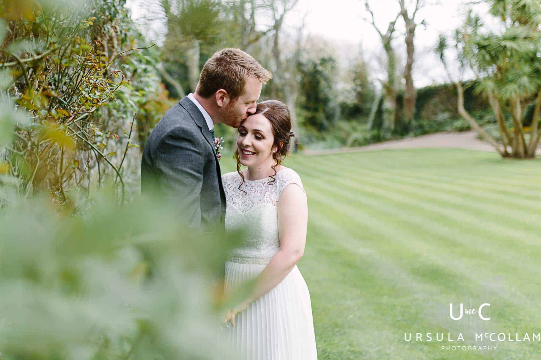 Groom kissing his bride in the garden at Ballygally Castle Hotel