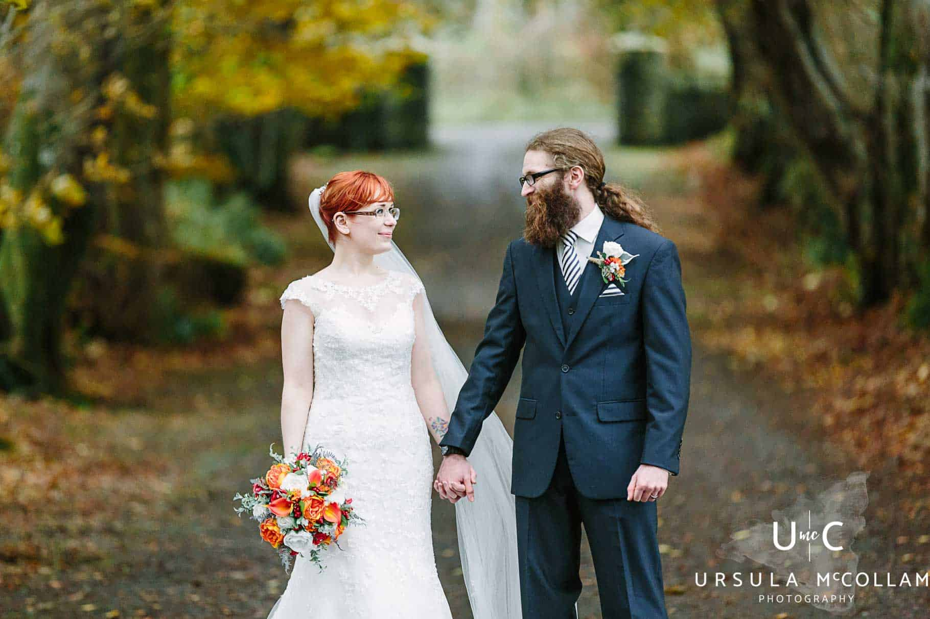 Bride and groom holding hands and looking at each other in the laneway of Breckenhill