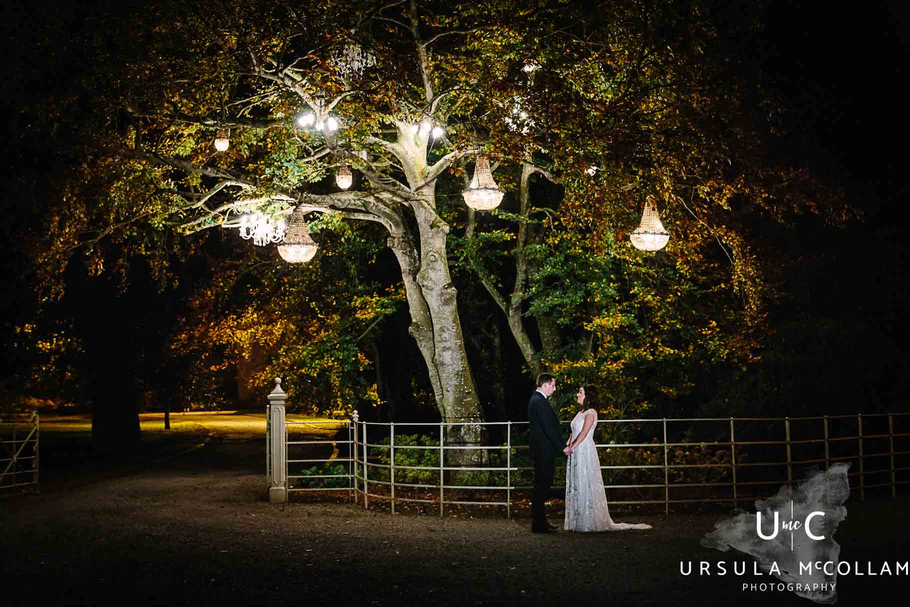Bride and groom holding hands in the dark under a tree with lanterns at Ballymagarvey Village by Ursula McCollam a Wedding Photographer in Northern Ireland