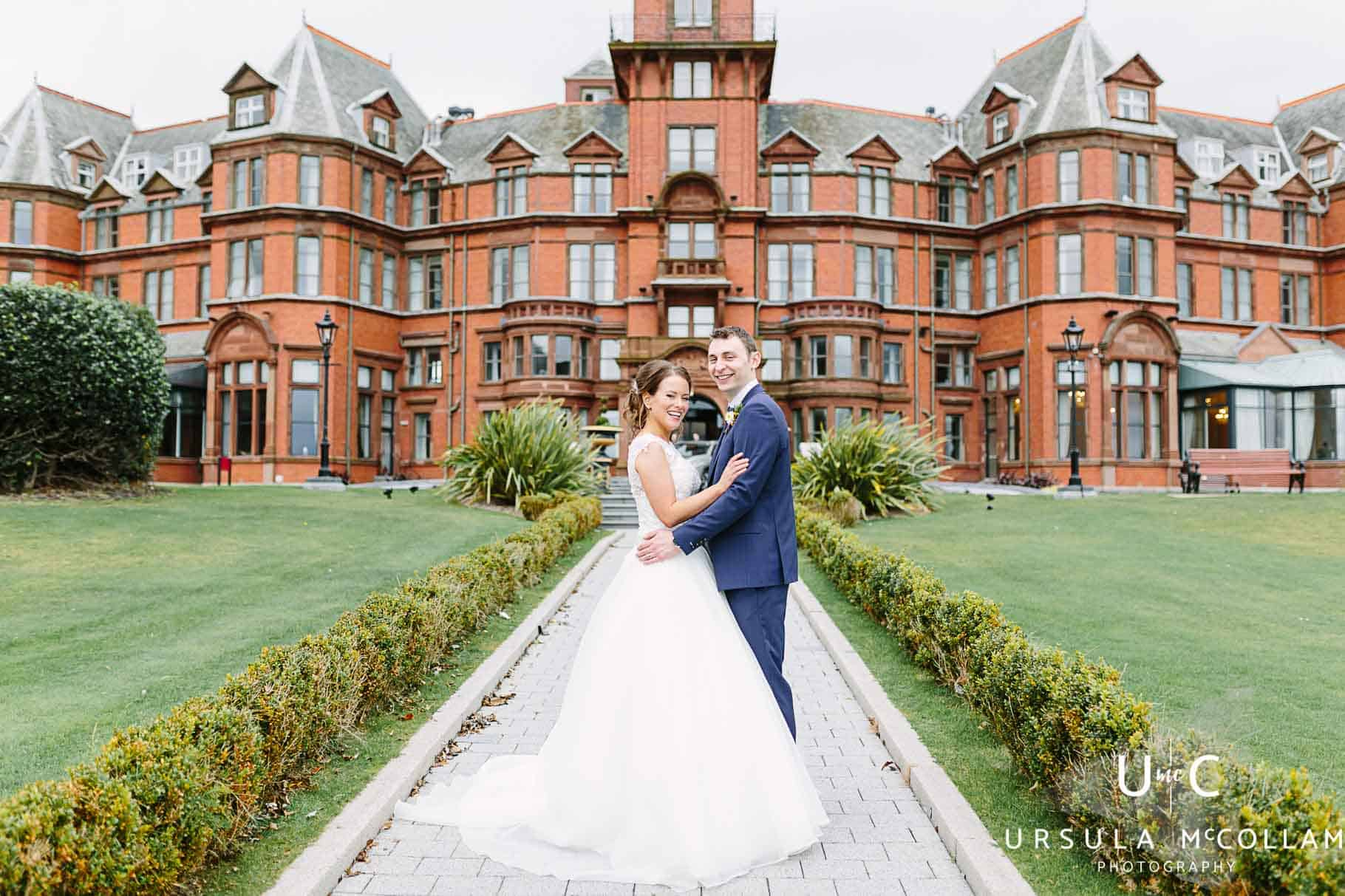 Bride and groom having a cuddle at the front of the Slieve Donard Hotel