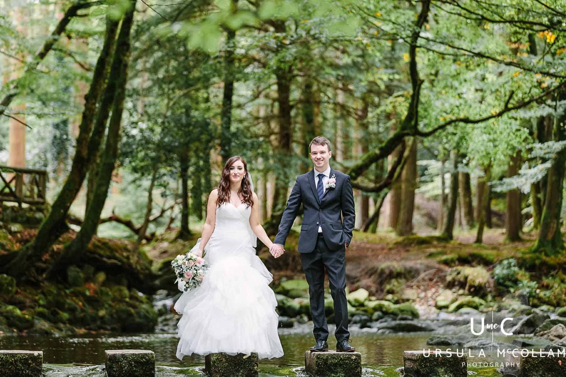 Bride and Froom holding hands at the stepping stones in Tolymore Forest, taken by Ursula McCollam an award winning wedding Photographer in Northern Ireland