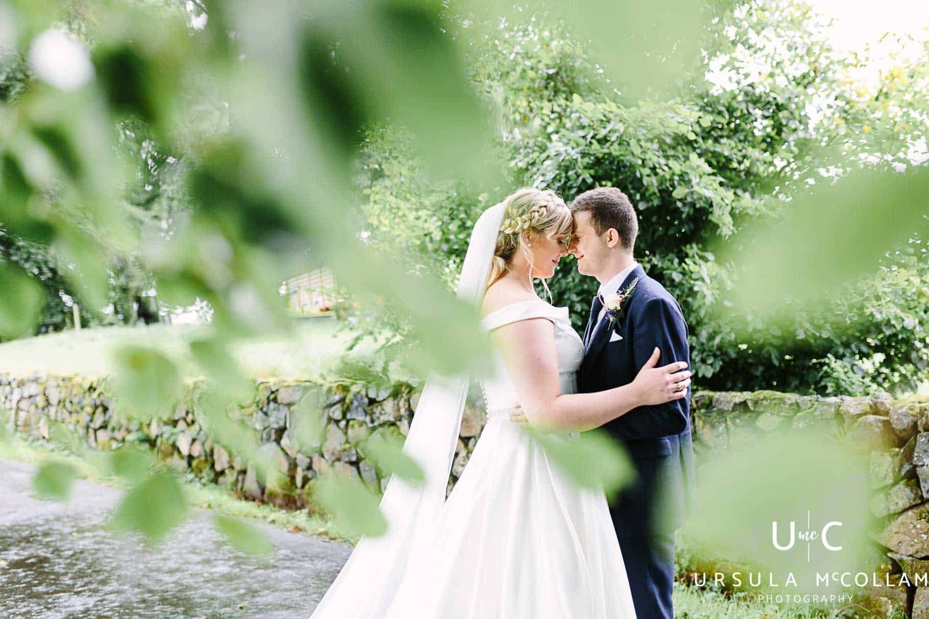 Bride and groom hidden by a tree