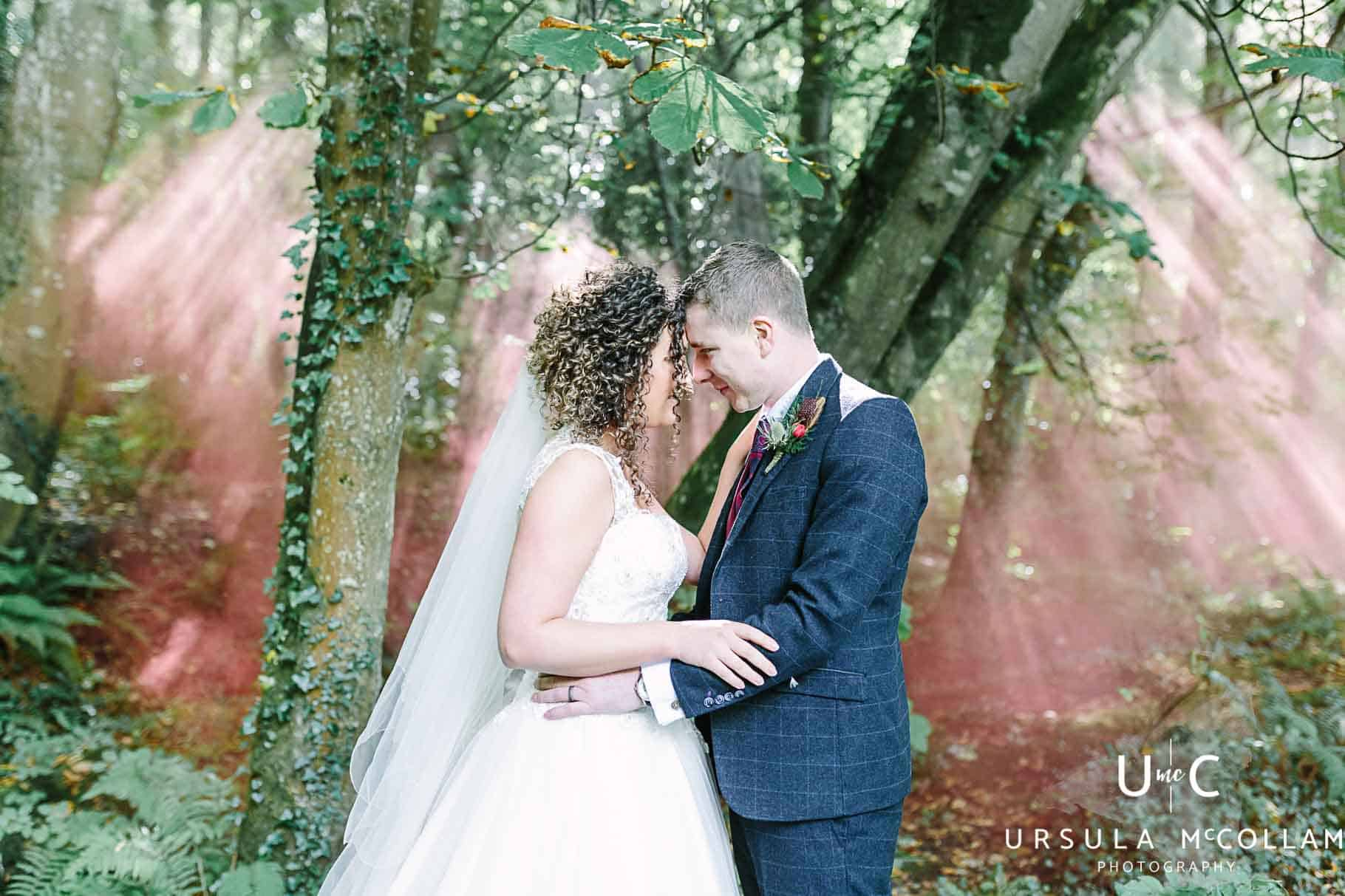 bride and groom in the forest with a red smoke bomb
