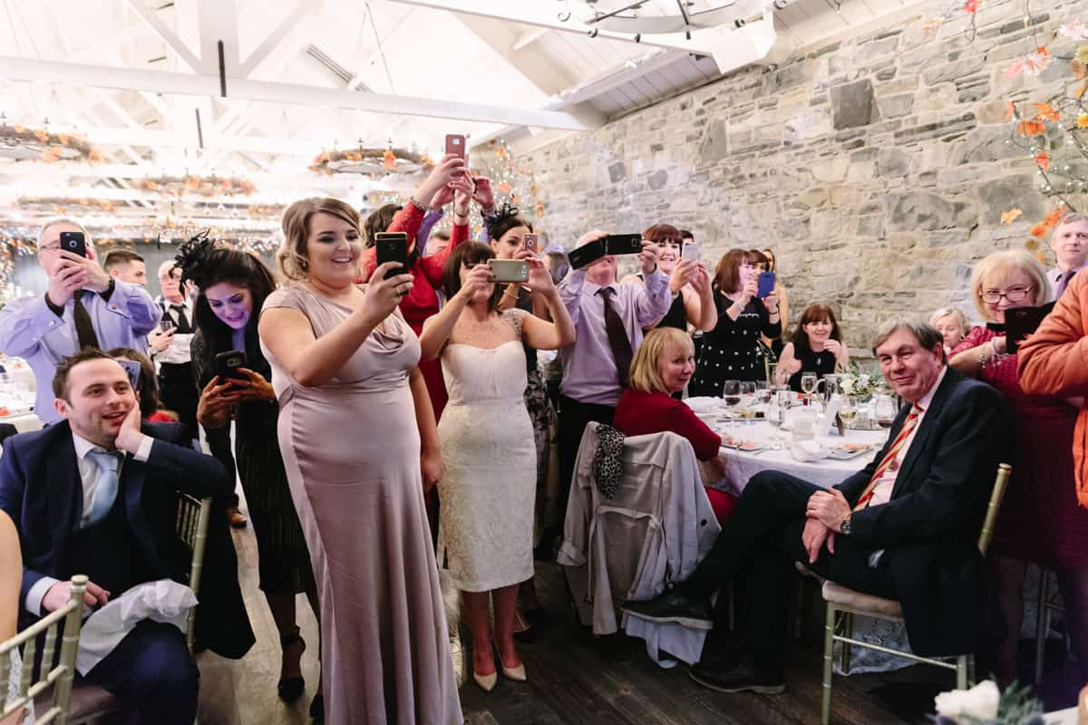 guests take photos of bride and groom cutting cake