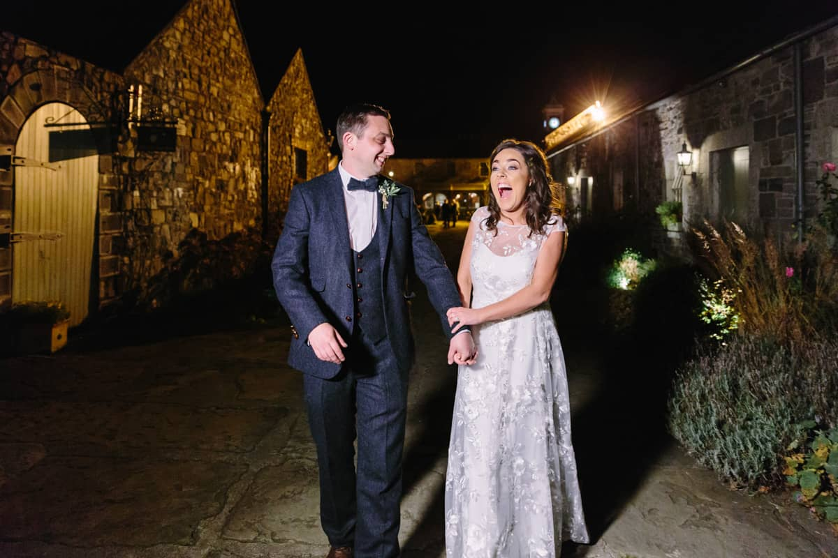 Bride and groom laughing at night