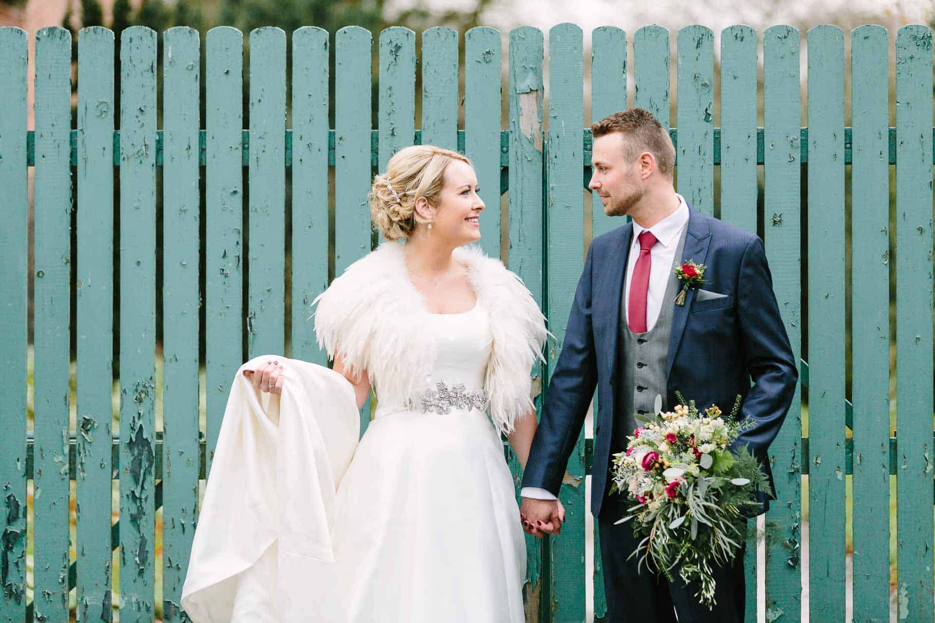 Bride and grool looking ar each other on front of an old painted gate