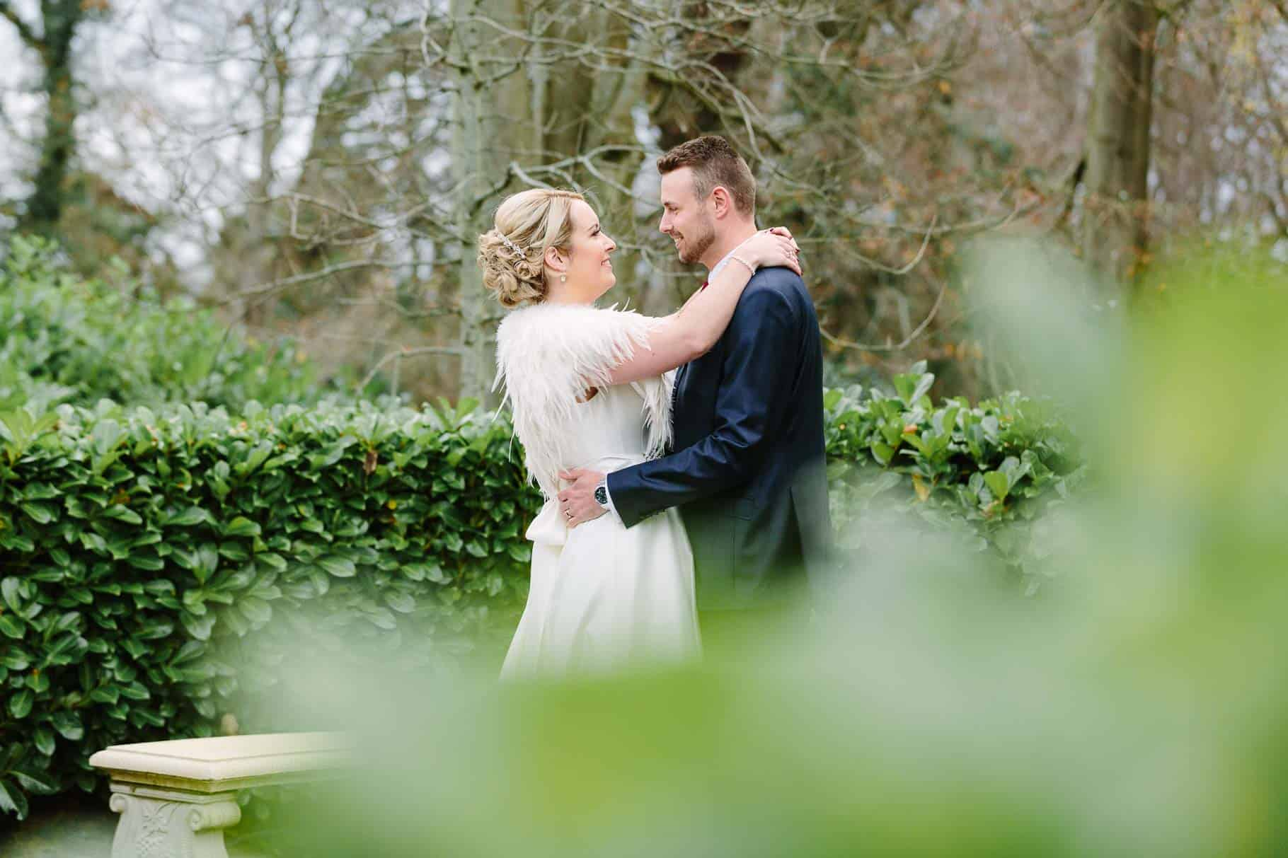 Bride and groom having a cuddle amongst the trees at clandeboye lodge