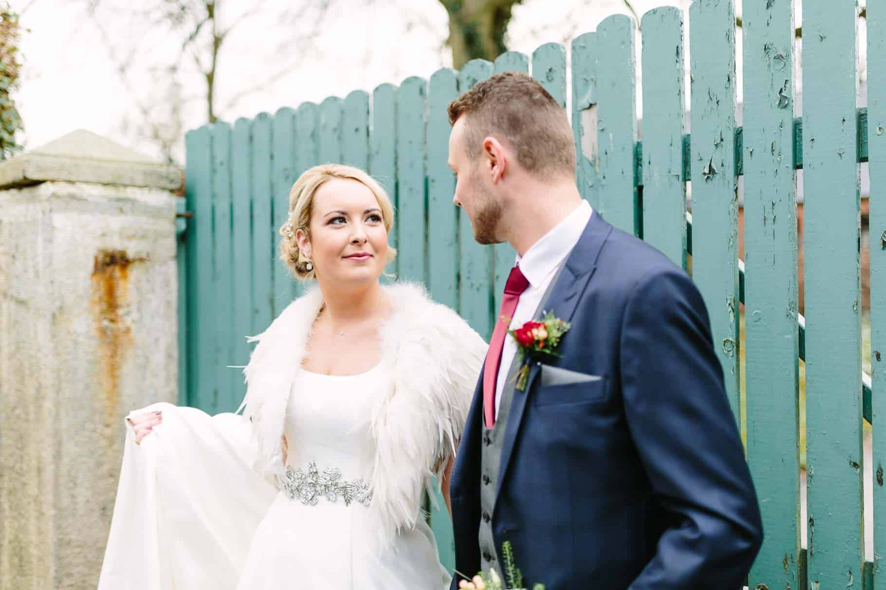Bride looking lovingly at her groom on fromt of an old aqua painted gate
