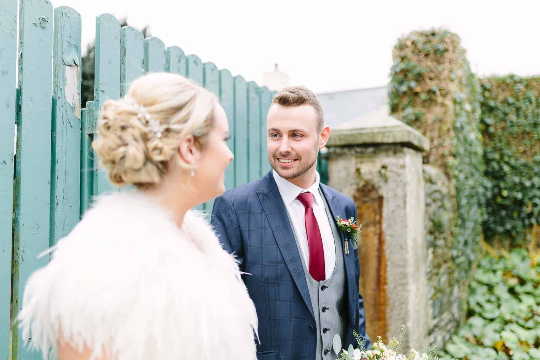 Groom looking at his bride in fromt of an old painted gate