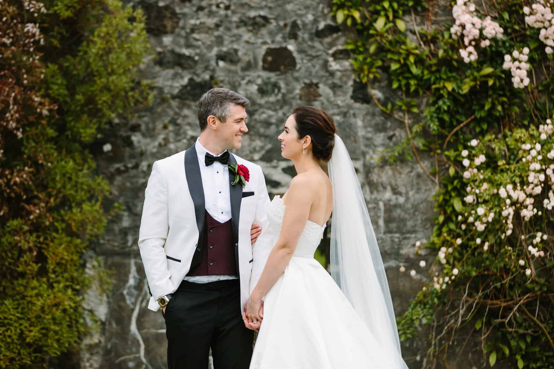 broom in white tuxedo jacket with his bride looking at each other