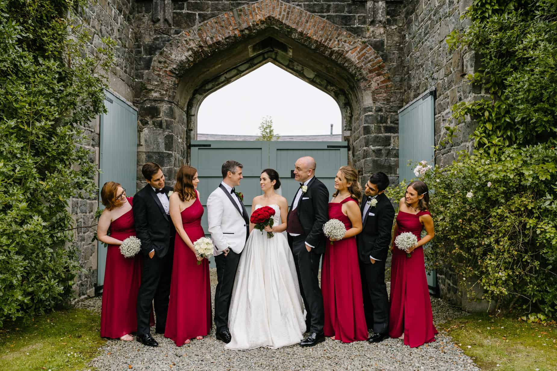 bridal party, bridesmaids in red dresses and men in tuxedos