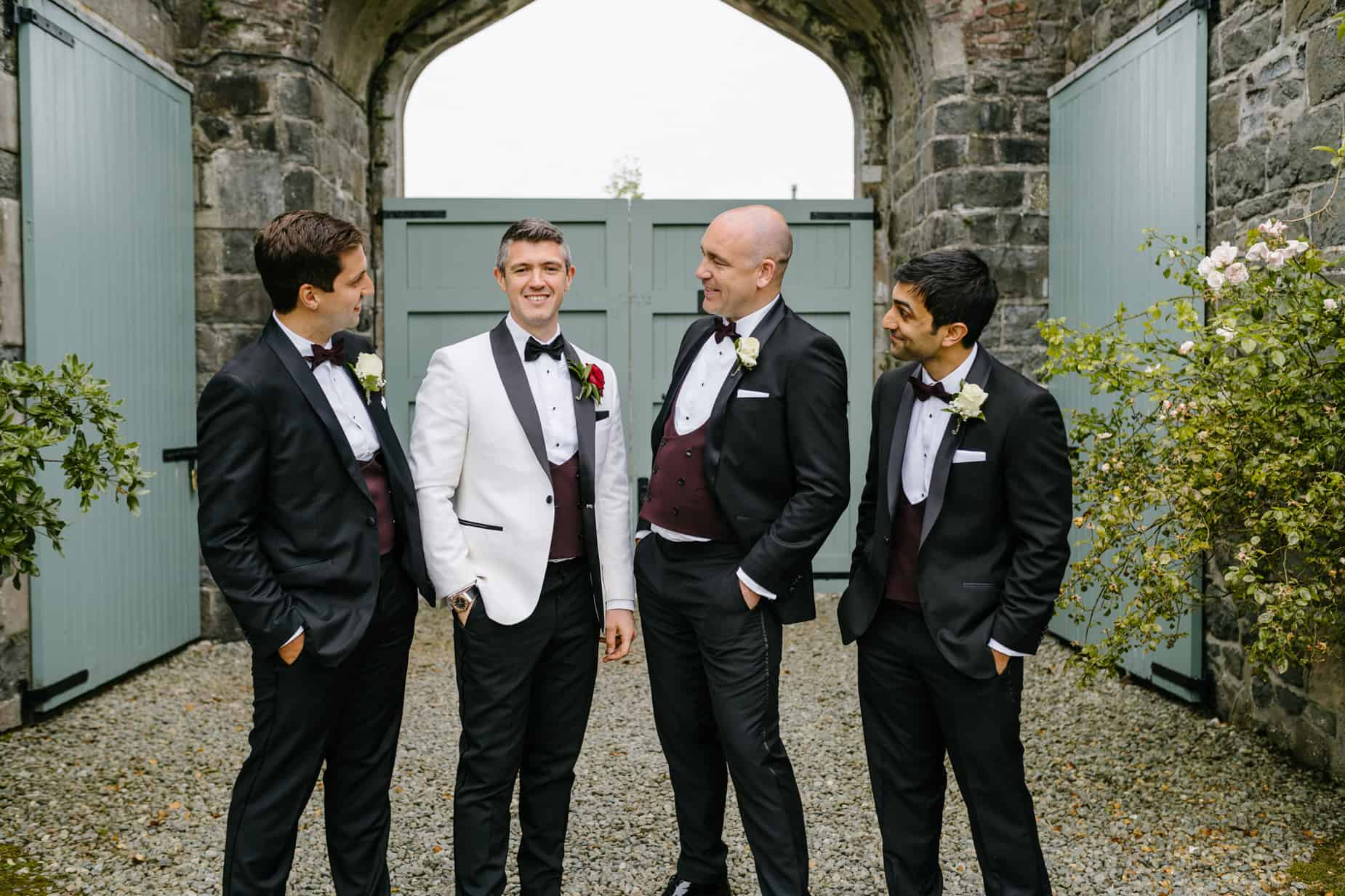 groom in tuxedo with white jacket and 3 grooms men in black tuxedos