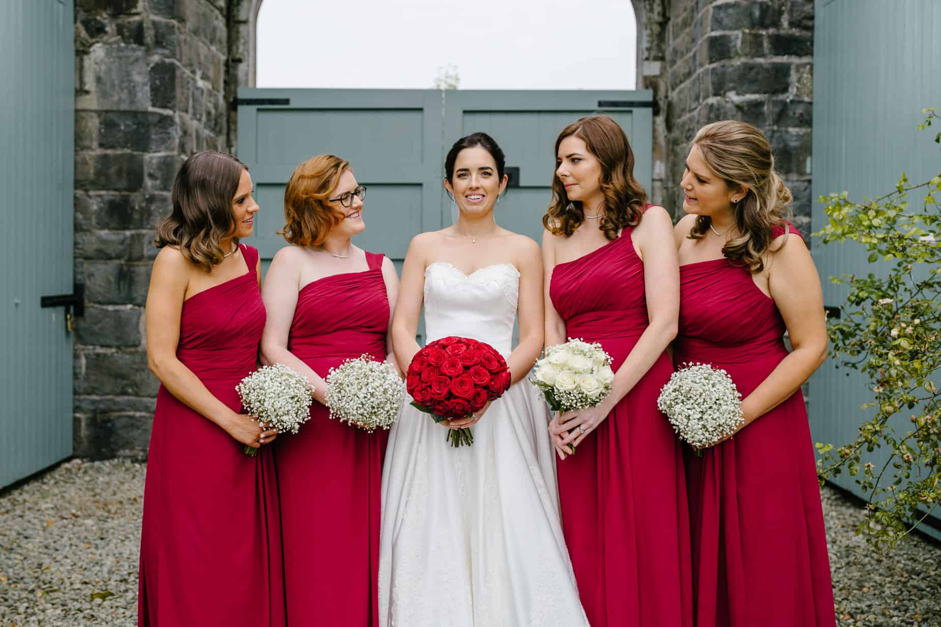 bride in white with her bridesmaids in red
