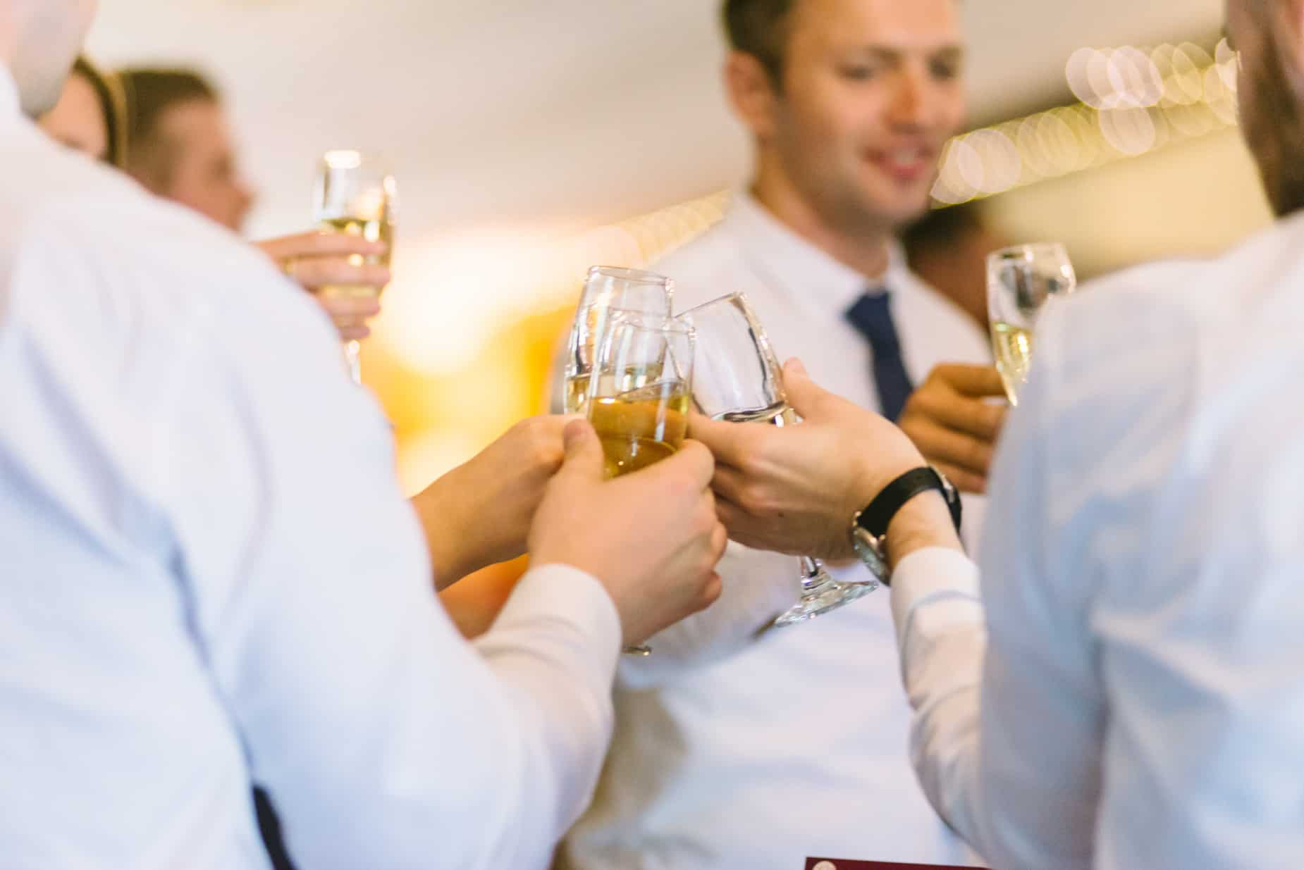 wedding guests clinking glasses during wedding speeches