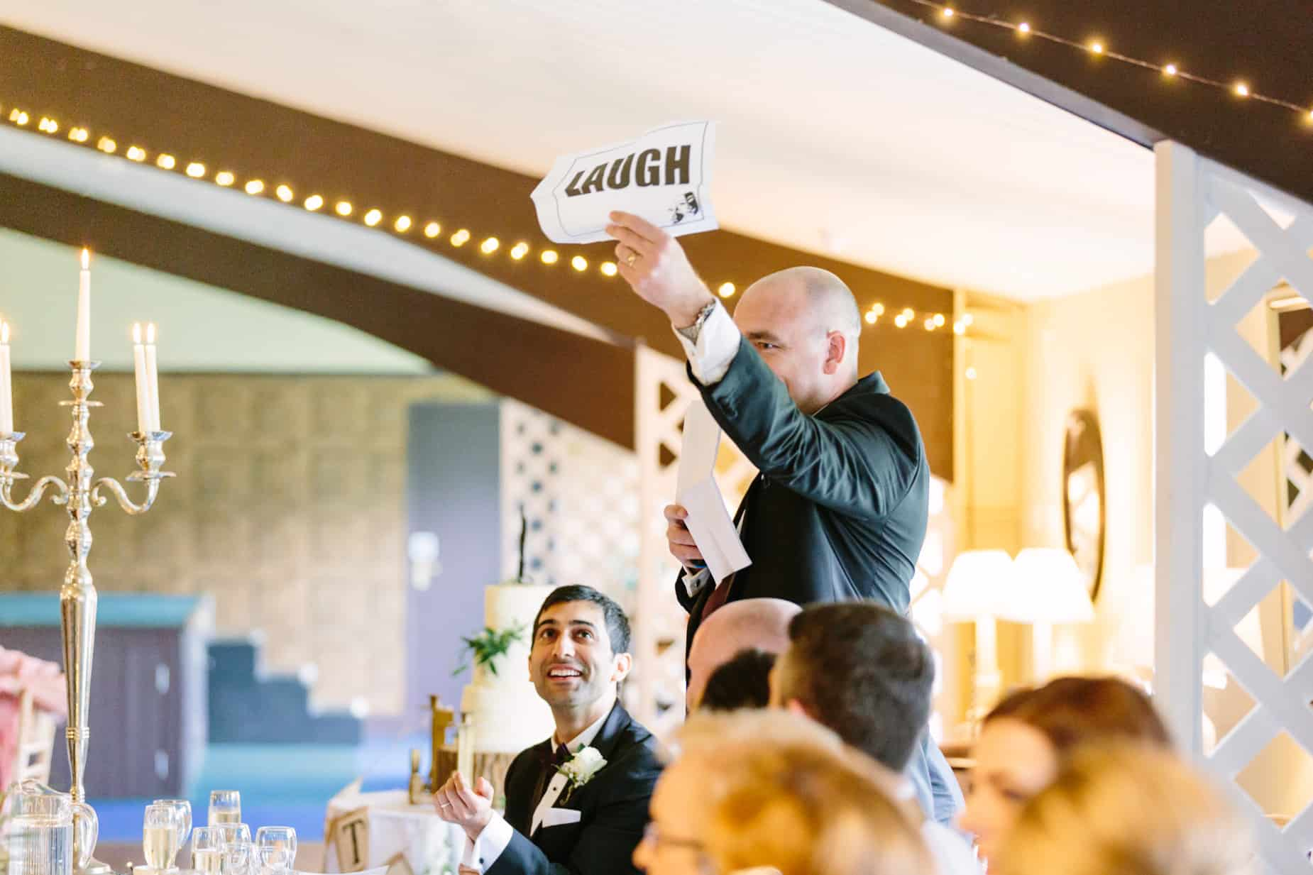 best man giving his wedding speech and holding up a sheet of paper asking guests to laugh