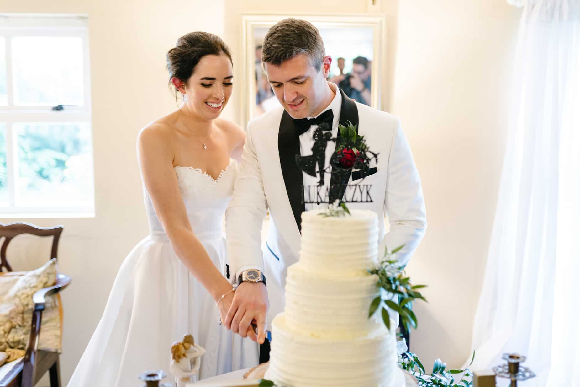 bride and groom in a white jacket cutting their wedding cake
