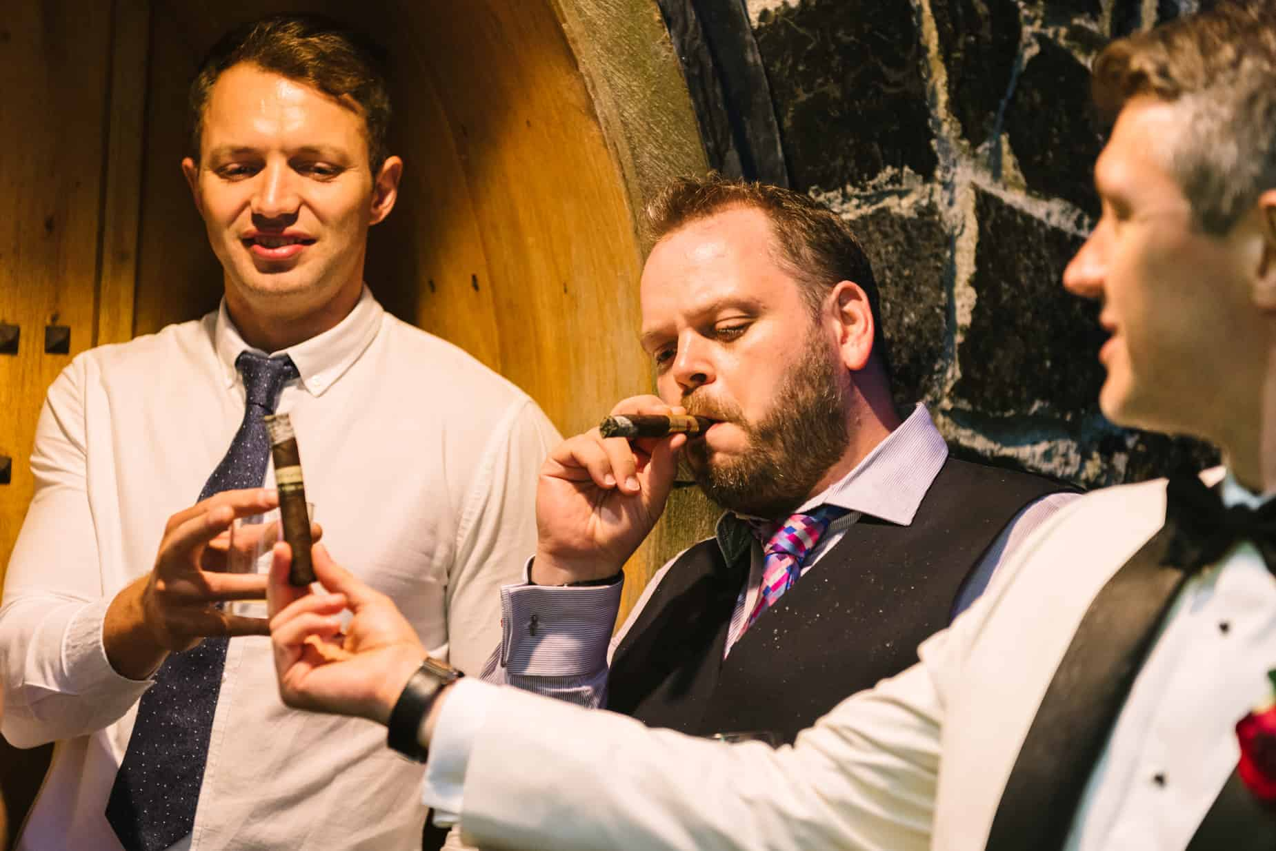 male guests enjoying wedding cigars