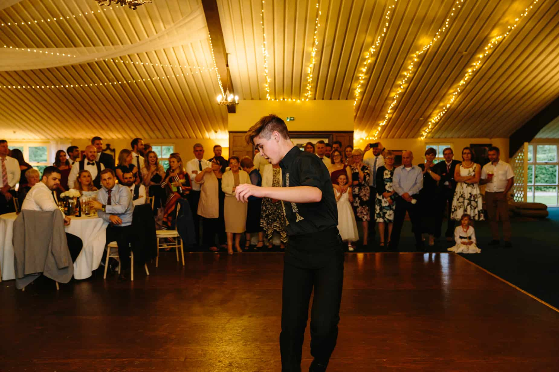 male Irish dancer dancing at wedding with guests watching
