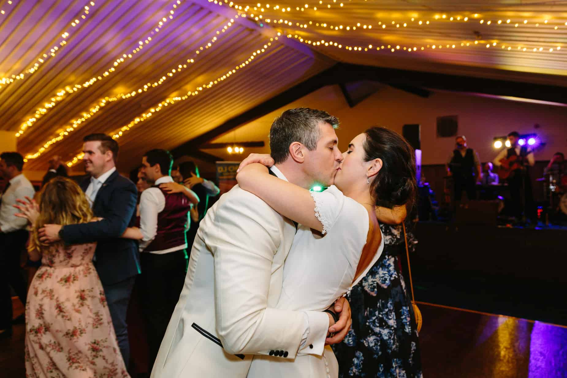 groom kissing bride on dance floor